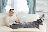 Smiling man relaxing with a laptop — Stock Photo