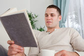 Man reading a book while holding a cup of tea — Stock Photo