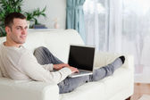 Man lying on his couch with a laptop — Stock Photo