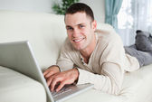 Smiling man lying on a couch with a laptop — Stock Photo