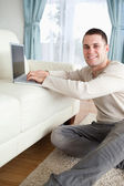 Portrait of a smiling man sitting on a carpet with a laptop — Stock Photo