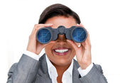 Assertive businesswoman looking through binoculars — Stock Photo