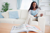 Donna usando la tavoletta sul divano — Foto Stock