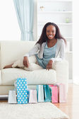 Woman on couch with shopping in front of her — Stock Photo