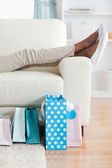 Woman on couch putting her feet up — Stock Photo
