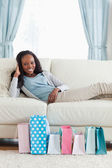 Woman relaxing on sofa after shopping — Stock Photo