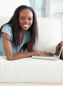 Close up of woman lying on the sofa with her laptop — Stockfoto