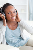Close up of woman enjoying music on the couch — Foto de Stock