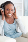 Close up of woman listening to music on sofa — Foto Stock