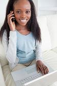 Närbild på kvinnan i telefonen medan du använder laptop — Stockfoto