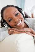 Close up of woman enjoying music on her sofa — Foto Stock