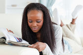 Woman looking at catalog on couch — Stock Photo