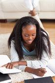 Mulher deitada no tapete na sala de estar fazendo lição de casa — Fotografia Stock