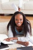 Femme allongée sur le tapis dans le salon, faire une critique du livre — Photo