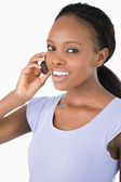 Close up of woman talking on the phone against a white backgroun — Stok fotoğraf