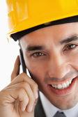 Заделывают улыбаясь архитектора, слушая клиентов по телефону — Стоковое фото