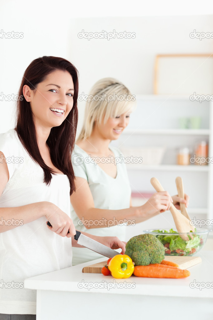 Joyful Women preparing dinner in a kitchen — Stock Photo #11190059