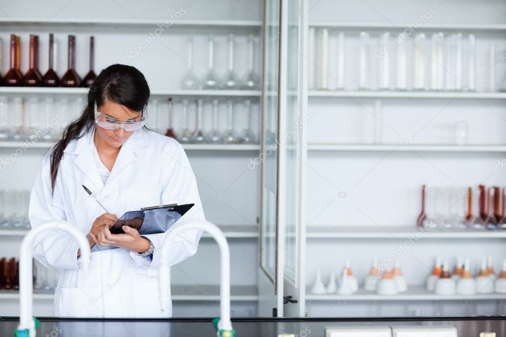 Focused female scientist writing on a clipboard in a laboratory  Stock Photo #11191170