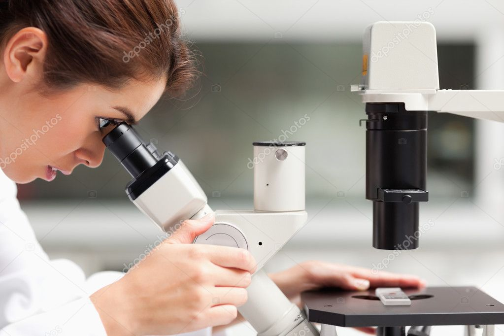 Close up of a female science student looking in a microscope in a laboratory — Stock Photo #11191395
