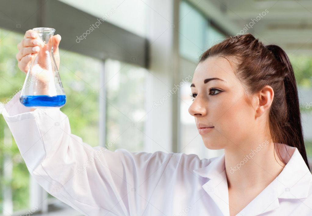 Cute science student looking at a blue liquid in an Erlenmeyer flask — Stock Photo #11191869