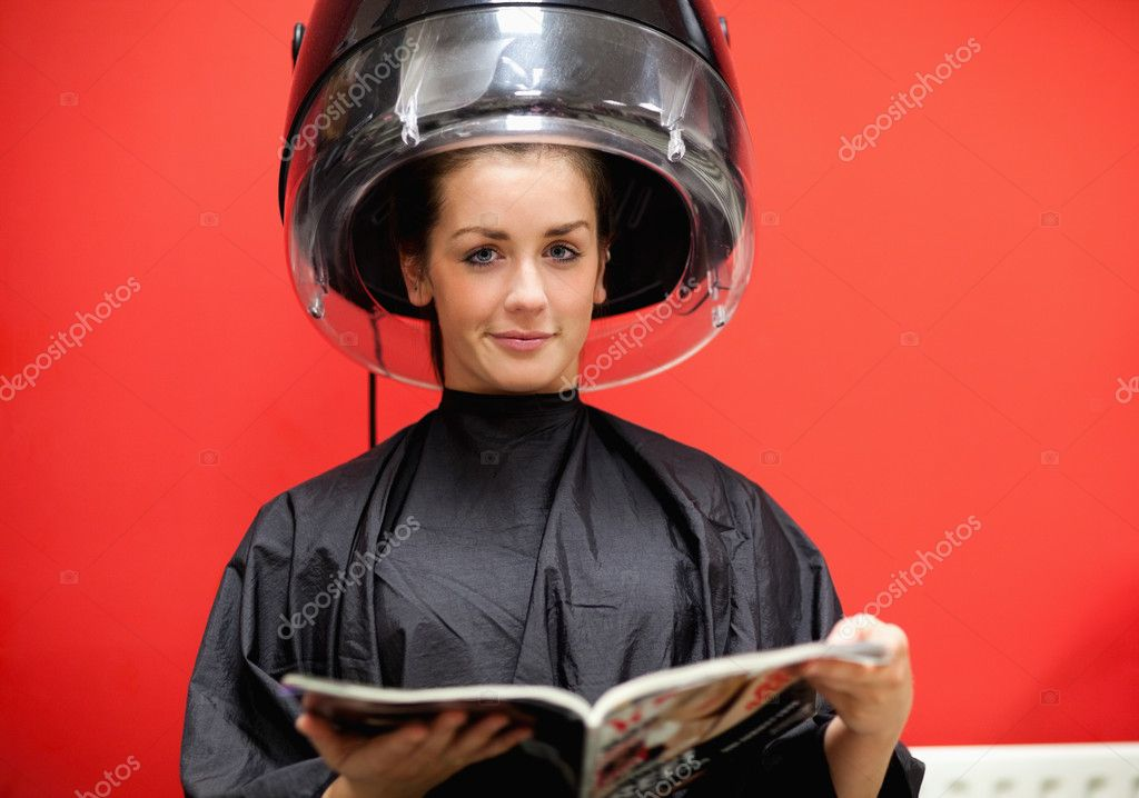 Young woman under a hairdressing machine while reading a magazine  Stock Photo #11193256