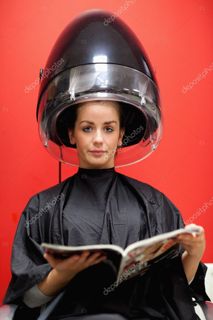 Portrait of a cute woman under a hairdressing machine while reading a magazine — Stock Photo #11193257