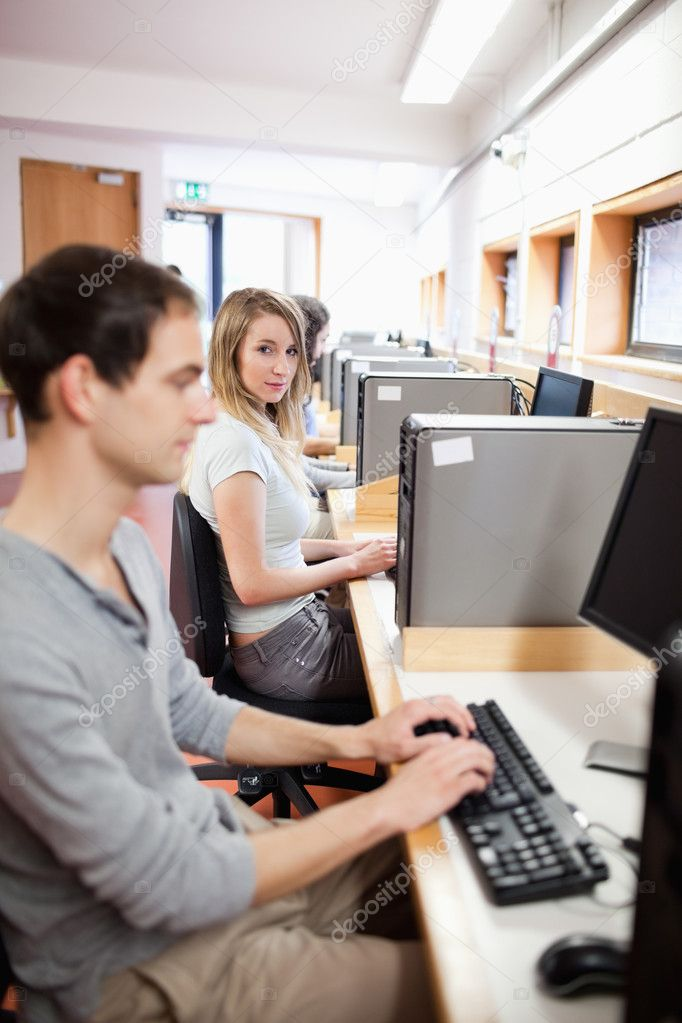Portrait of a fellow students using a computer in an IT room — Stock Photo #11193918