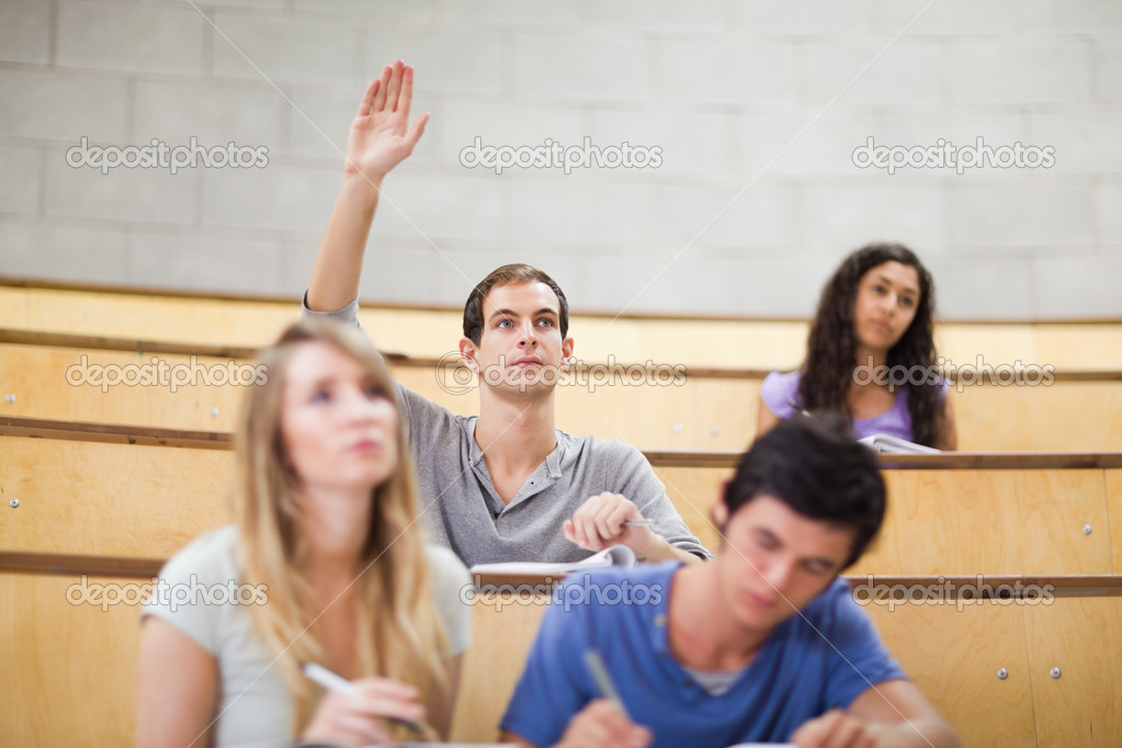 Student raising his hand while his classmates are taking ...
