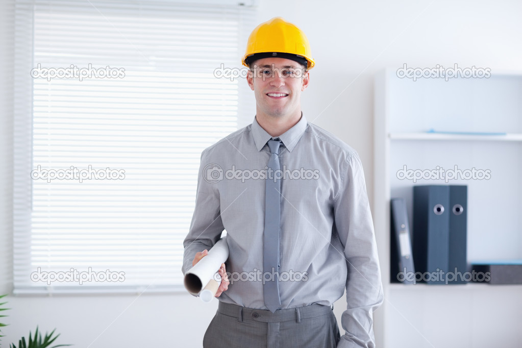 Architect wearing helm and carrying plans in his office — Stock Photo #11194632