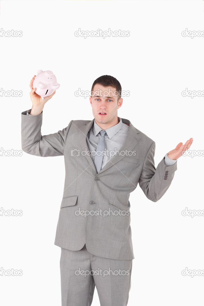 Portrait of a broke businessman shaking an empty piggy bank against a white background — Stock Photo #11196205