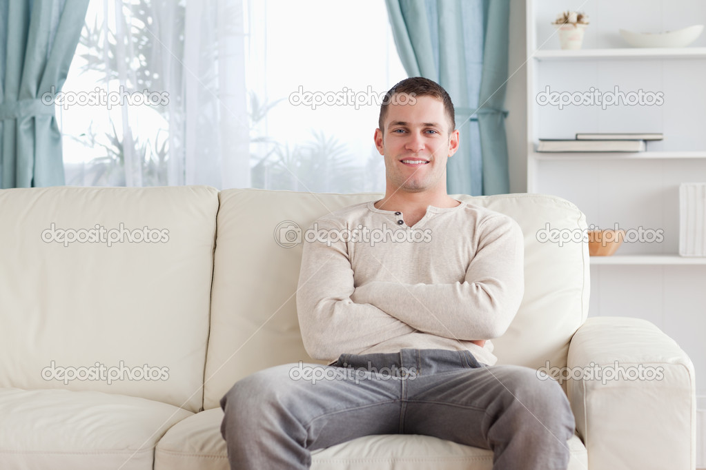 man sitting on a couch stock photo wavebreakmedia. Black Bedroom Furniture Sets. Home Design Ideas