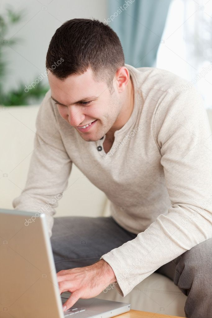 Portrait of a smiling man using a notebook in his living room — Stock Photo #11196940