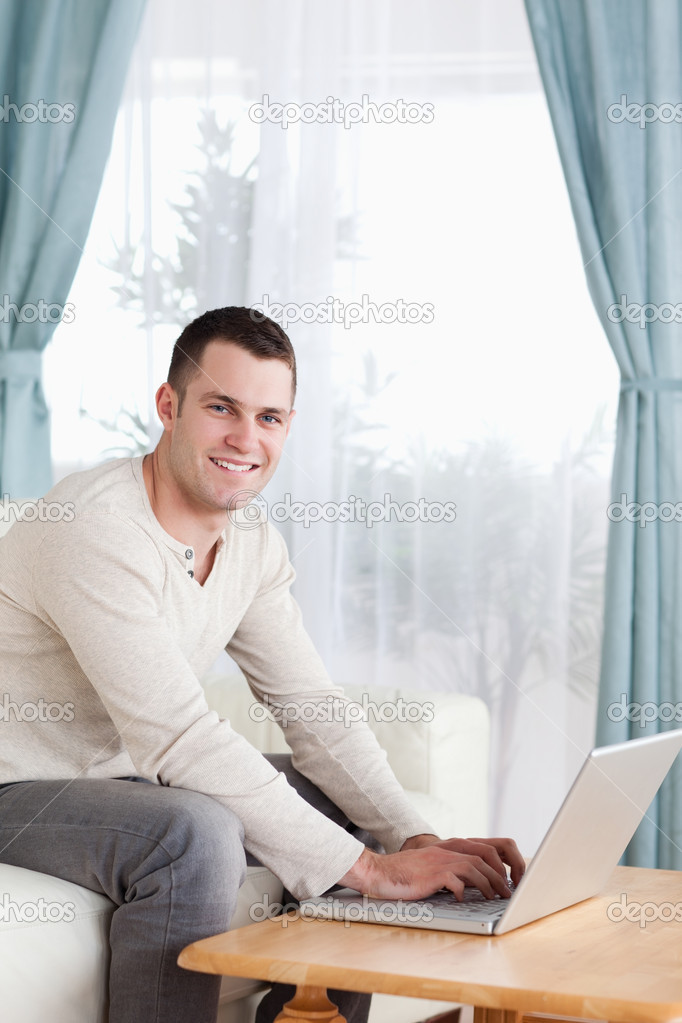 Portrait of a smiling man typing on his laptop in his living room — Stock Photo #11197057