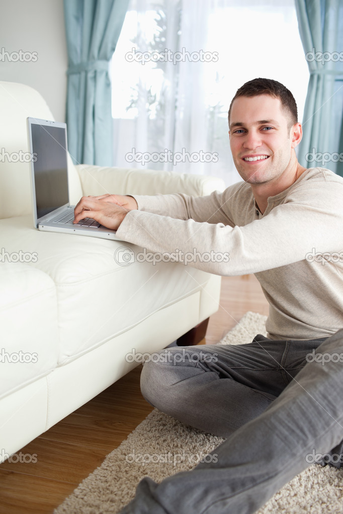 Portrait of a smiling man sitting on a carpet with a laptop while looking at the camera — Stock Photo #11197228