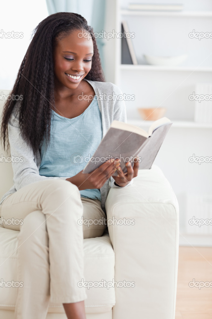 Smiling woman reading a book on her sofa — Stock Photo #11197740