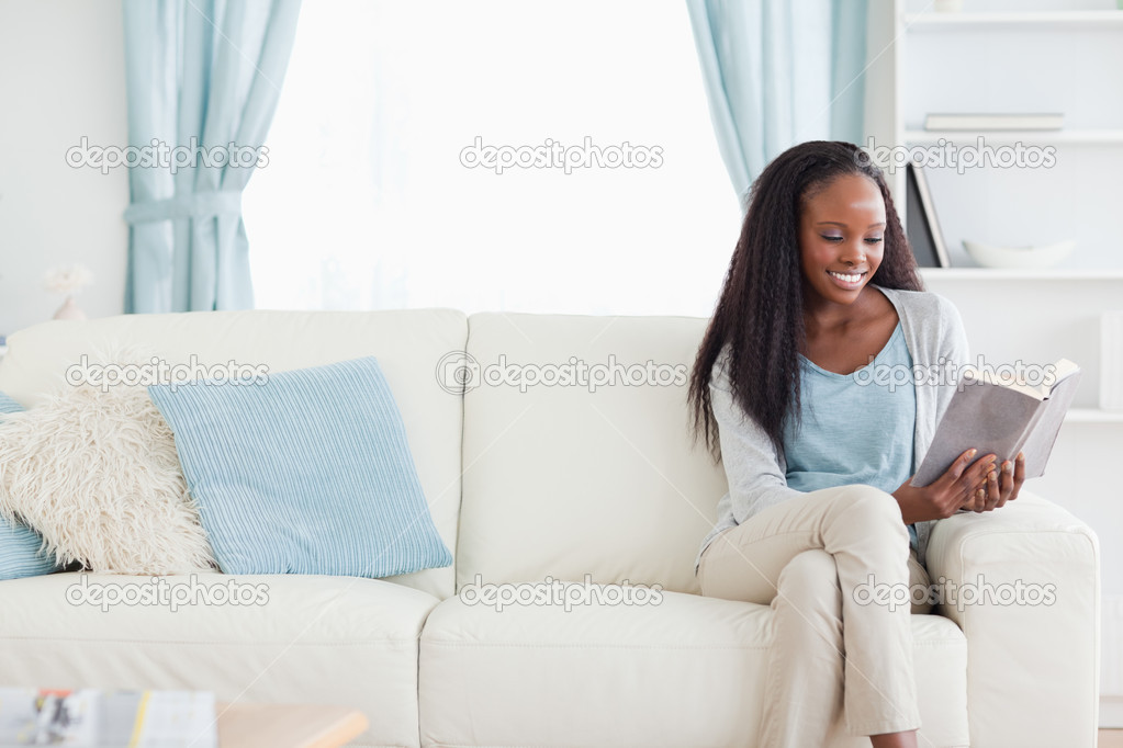 Smiling woman reading a book in living room  Stock Photo #11197751