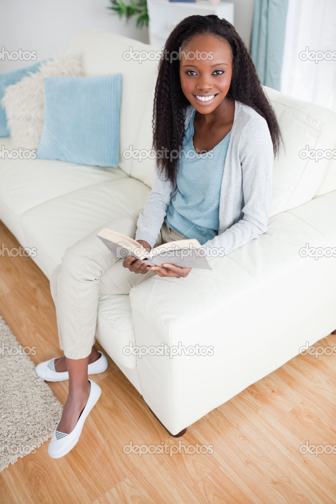 Smiling woman reading a book in the living room — Stock Photo #11197752