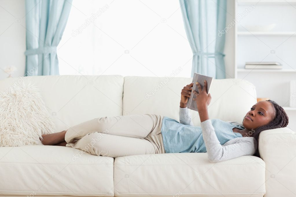Young woman lying on sofa reading — Stock Photo #11197800