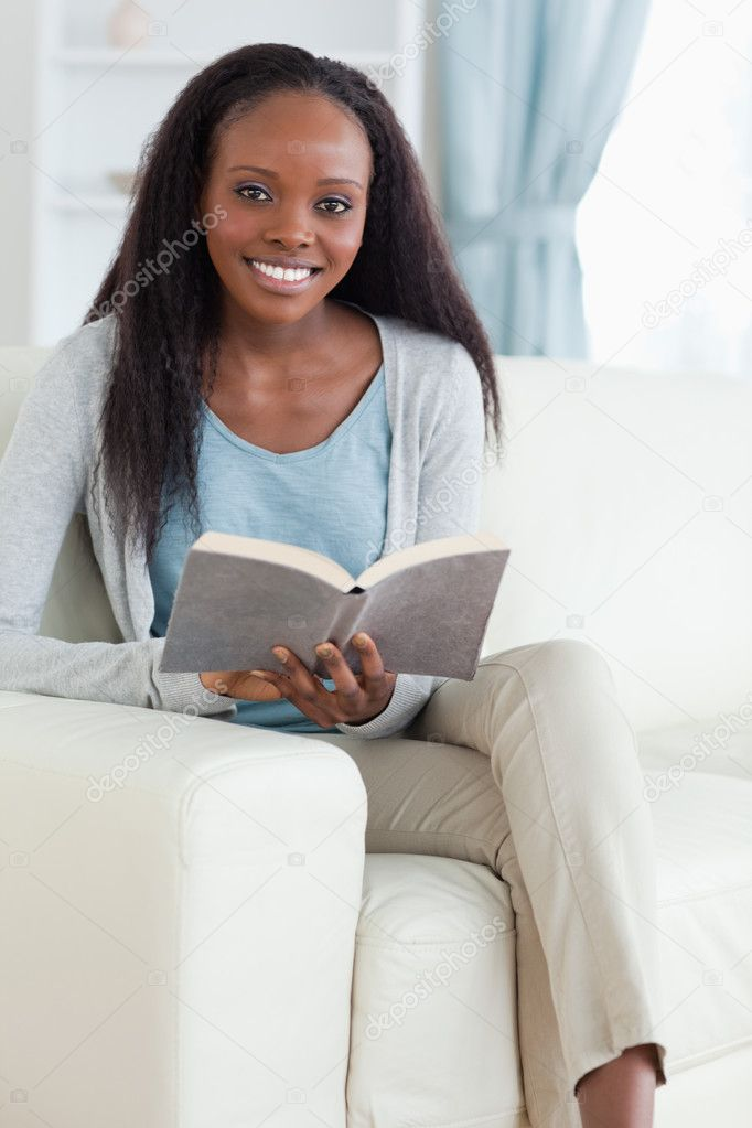 Smiling woman with book on sofa — Stock Photo #11198069