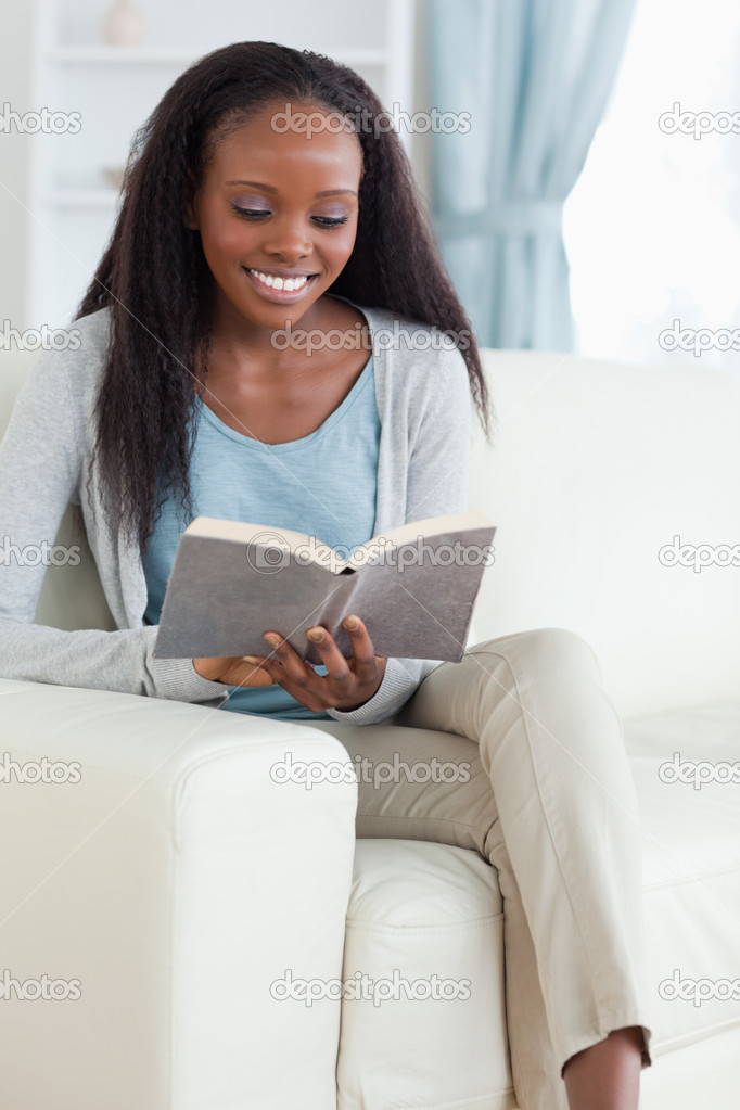 Smiling woman with book on couch — Stock Photo #11198072