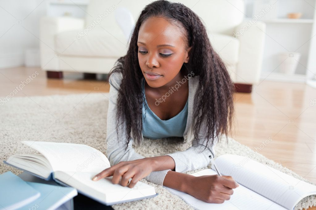 Young woman lying on the floor doing homework — Stock Photo #11198352