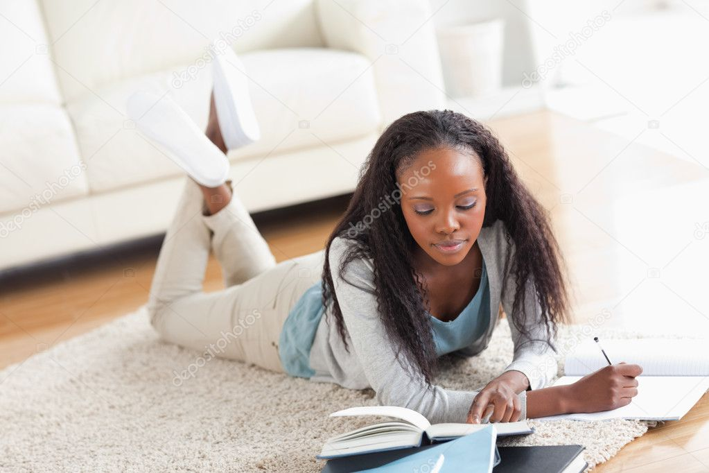 Young woman lying on carpet doing a book review — Stock Photo #11198360