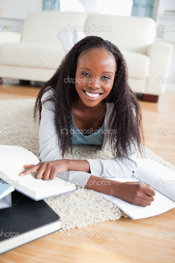 Smiling young woman lying on carpet doing a book review — Stock Photo #11198365