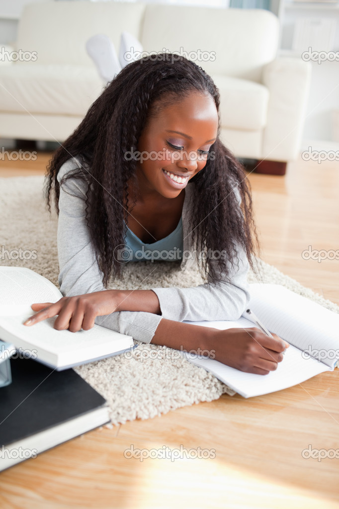 Young smiling woman lying on the floor doing her homework — Stock Photo #11198367
