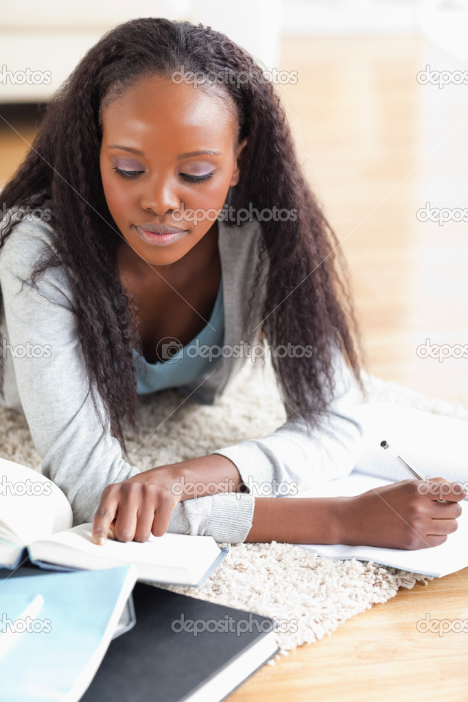 Close up of young woman lying on the floor doing her homework — Stock Photo #11198369