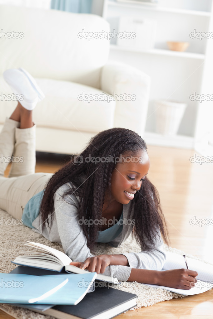 Smiling woman lying on the floor taking notes  Stock Photo #11198372