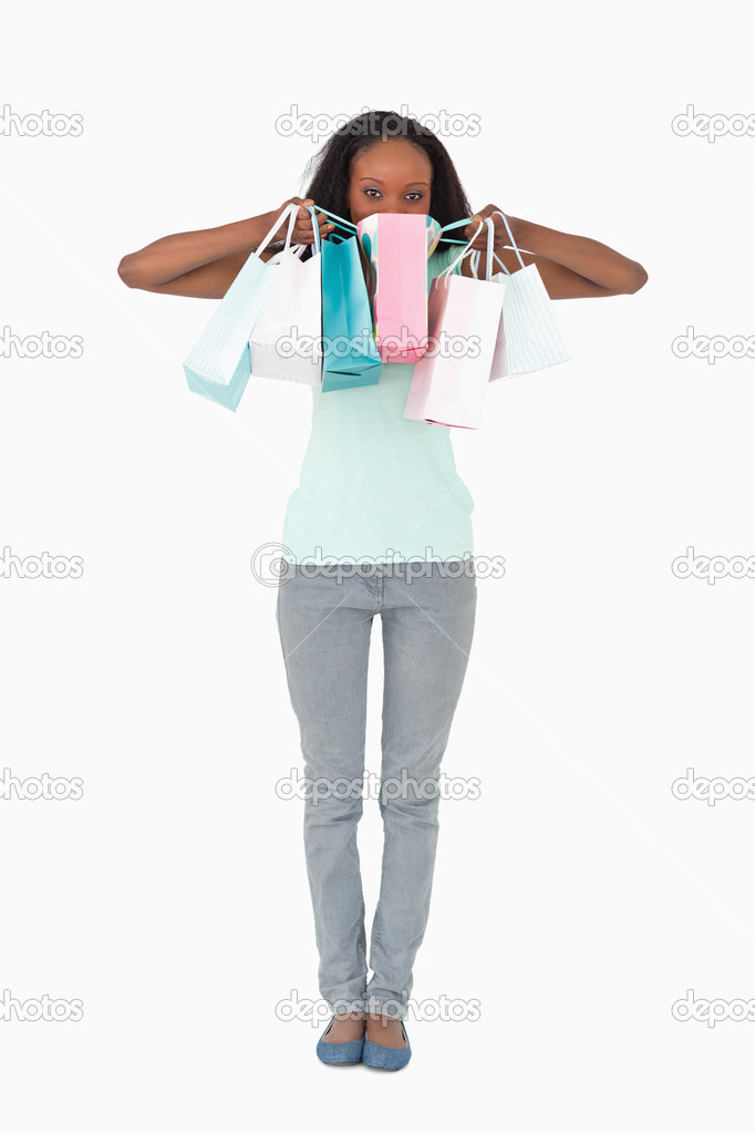 Young woman hiding behind her shopping on white background  Stock Photo #11198502