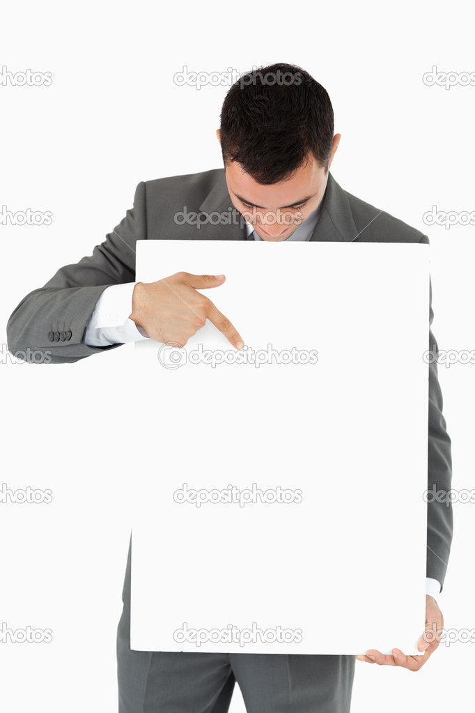 Businessman pointing at sign he is presenting against a white background — Stock Photo #11199363