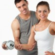 Portrait of a smiling man helping a woman to work out — Stock Photo #11200921
