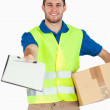 Smiling young delivery man with packet asking for signature — Stock Photo